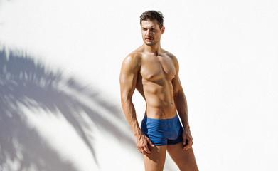 Muscular man wearing blue beach shorts and posing