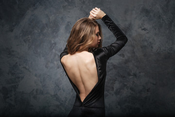 Seductive young woman in evening dress with open back