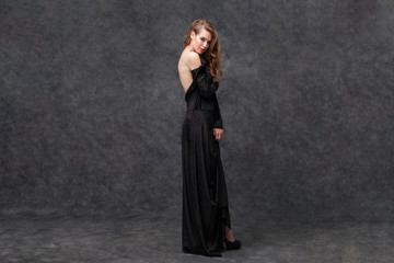 Tempting lovely woman in long black dress with open back