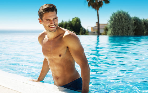 Photo of handsome smiling man in swimming pool in summer scenery