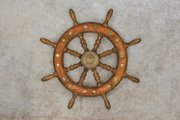 Vintage wooden ship steering wheel on a retro background