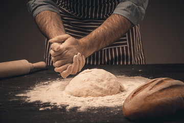 Male hands knead the dough.