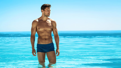 Panoramic photo of sexy man posing in swimming pool