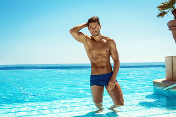 Handsome male model wearing blue beach shorts and posing in swim