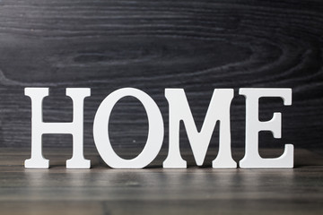 White letters with word HOME on wooden surface