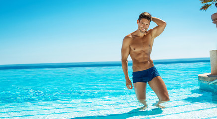 Summer photo of muscular smiling man in swimming pool