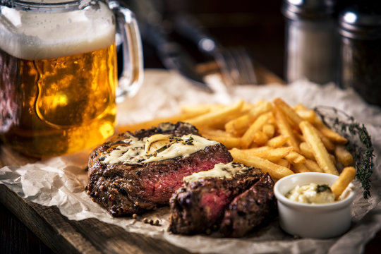 Healthy lean grilled medium-rare steak with french fries, beer