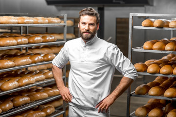 Portrait of handsome baker at the bakery with breads and oven on the background