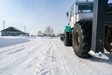 Tractor rides through village in winter