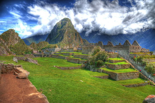 Colorful HDR image of tourists visiting the ruins in Machu Picchu, the lost Incan City of Machu Picchu near Cusco, on a clear blue sky