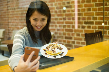 Woman take self photo with her dessert