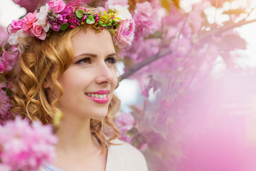 Woman with flower wreath against pink tree in blossoom