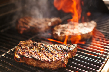 Photo sur Plexiglas Grill, Barbecue steaks cooking over flaming grill