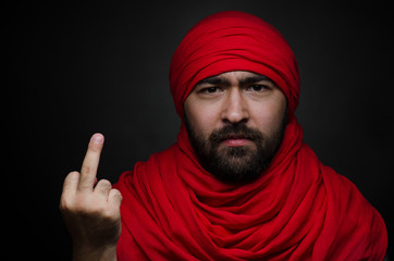 Turkish and Arabic theme: beautiful Arabic man with a beard in a red scarf showing gestures isolated on black background in studio