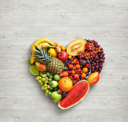 Heart symbol. Fruits diet concept. Food photography of heart made from different fruits on white wooden table. High resolution product.