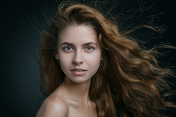Dramatic portrait of a girl theme: portrait of a beautiful girl with flying hair in the wind against a background in studio