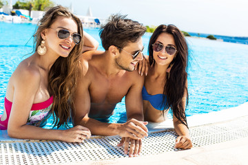 Group Of Smiling Friends Having Fun In Swimming Pool And Wearing