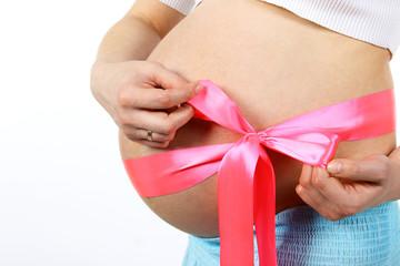 живот беременной девушки с розовым бантом