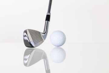 Golf club and golf ball on the glass desk
