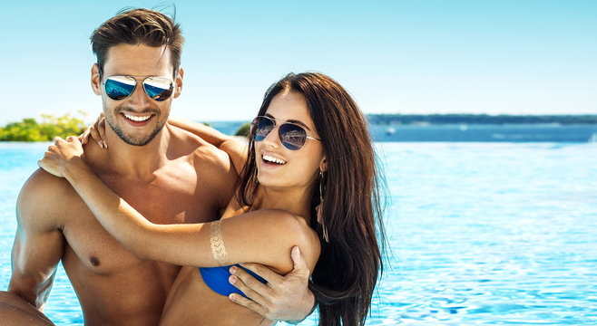 Portrait of handsome smiling couple having fun in swimming pool