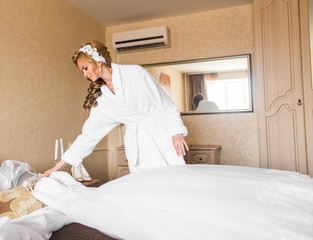 The bride in white bathrobe. Wedding preparations.