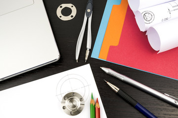 Drawings, components and design tools on the table of an engineer or designer illustrating research and development process in engineering and science.