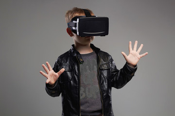 little Boy in virtual reality glasses playing the game.3D VR glasses cardboard