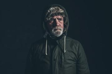 Senior man with gray beard wearing dark green winter coat with h