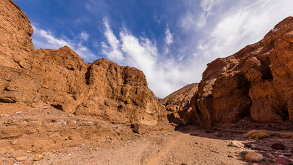 Narrow canyon with vertical walls on both sides. Rocky landscape background. Natural bridge canyon trail, Death Valley