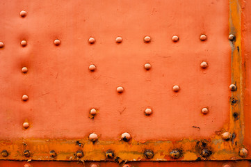 Old faded red metal background with studs