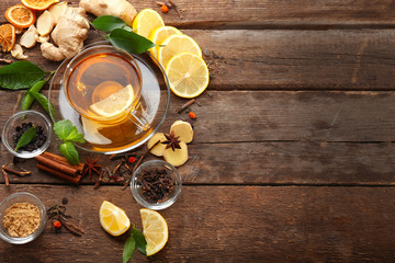 Cup of tea with ginger and cinnamon on wooden background