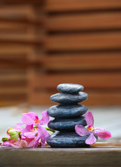 Stack of spa stones with pink orchids on wooden wet bridge
