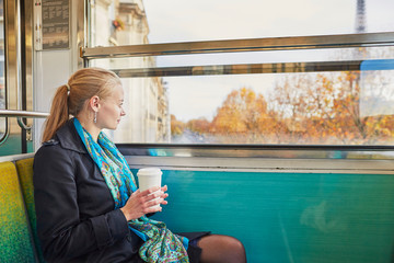 Beautiful young woman travelling in a train of Parisian underground and drinking coffee