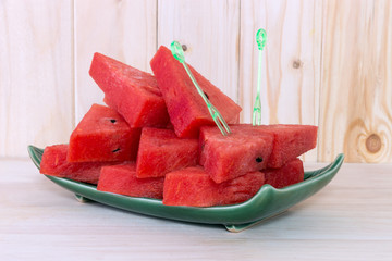sliced watermelon on green plate on wooden background