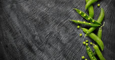 Green peas on black stone