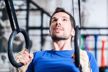 Mann an Ringen bei Sport Training im Fitnessstudio