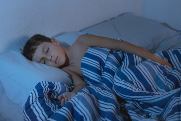 Portrait of a little boy sleeping in the bedroom at night