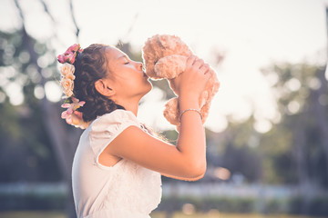 Girl kissing her toy bear, side view