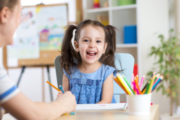 Child little girl laughing, painting colorful pencils at her playtable