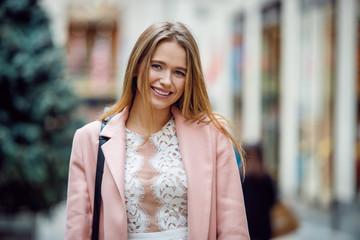 Portrait of happy beautiful caucasian woman on city street