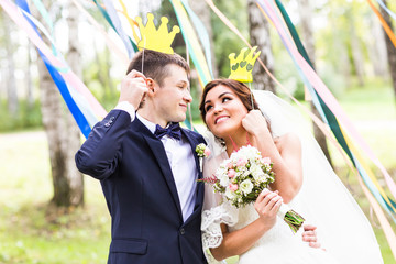 April Fools' Day. Wedding couple posing with crown, mask.