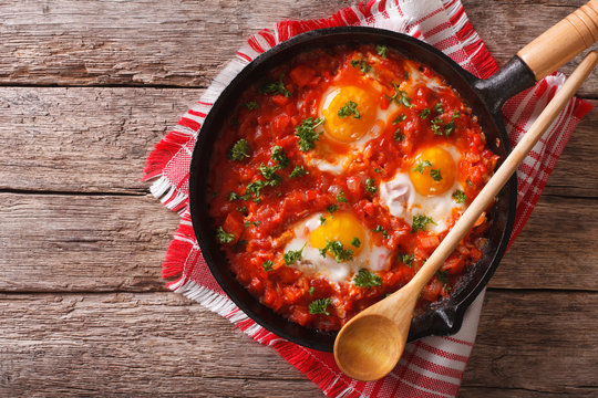 Shakshuka breakfast of fried eggs and tomatoes in a pan. horizontal top view