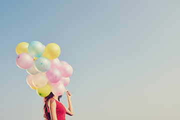 Girl with many colorful balloons against blue sky