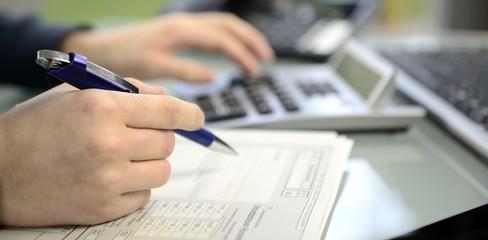 Frau kalkuliert mit Taschenrechner Umsatzsteuer