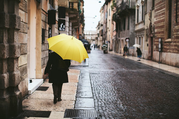 Woman with yellow umbrella is back on the streets of Verona