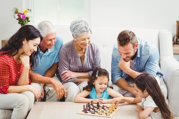 Parents and grandparents looking at girls playing chess