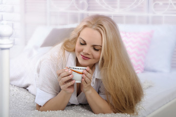 Girl lying in bed with a cup of coffee.
