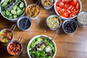 ассорти из сухофруктов, нарезанных овощей, семян на деревянном столе.