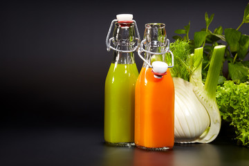 Bottles with fresh vegetable juices isolated on black. Detox die