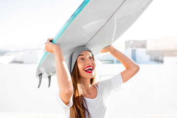 Portrait of a young smiling woman dressed casual carrying surfboard on the white city background. Active water sport vacations